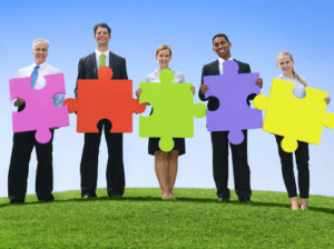 Free Coaching Exercises shown by people standing holding colourful jigsaw pieces