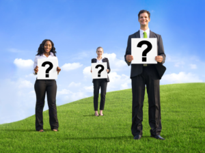 Free Coaching Questions shown by 3 people standing holding question marks