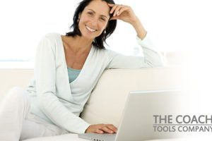 Relaxed Coach using Balance& Self-Care Tools on Sofa with Laptop