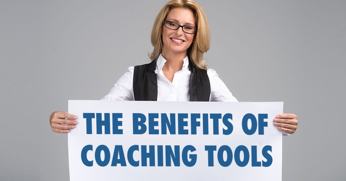 Coach holding sign that says The Benefits of Life Coaching Tools