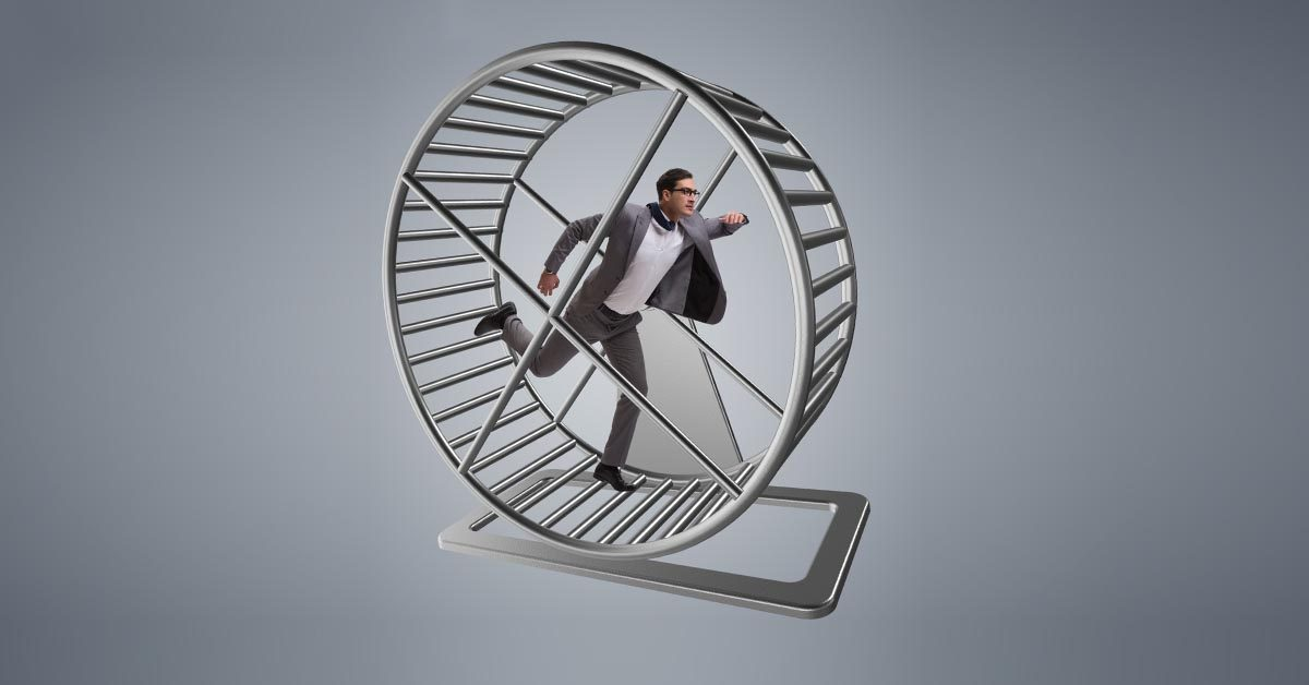 Business Man in Grey Suit Runs on Hamster Wheel